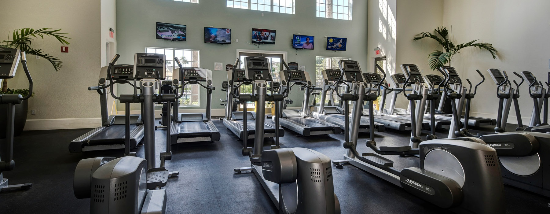 spacious and bright fitness center filled with equipment